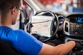 istock Automobile computer diagnosis. Car mechanic repairer looks for engine failure 1190638689