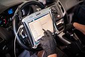 istock Automobile computer diagnosis. Car mechanic repairer looks for engine failure 1192264049
