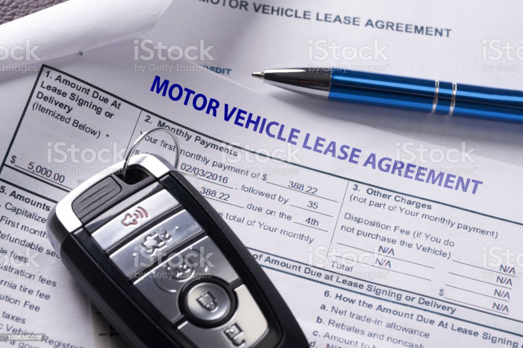 Automobile lease agreement document with key and pen on contract