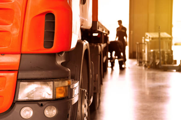 automobile mechanic checking truck in the garage with sunbeam, selective focus - truck tire foto e immagini stock