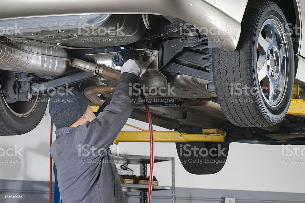 Automobile Mechanic Working Under Raised Car royalty-free stock photo