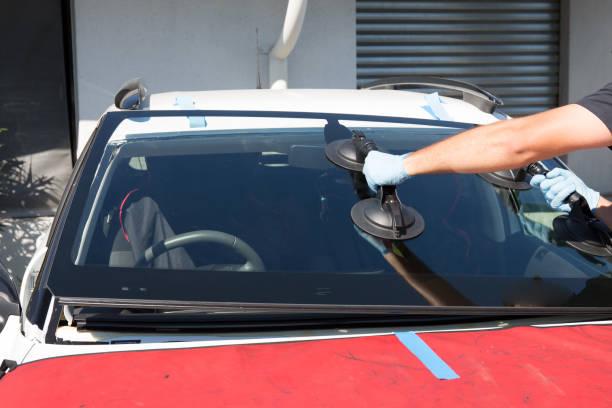automobil spezielle arbeitnehmer glaser ersetzen frontscheibe windschutzscheibe des autos in der straße - fensterbauer stock-fotos und bilder