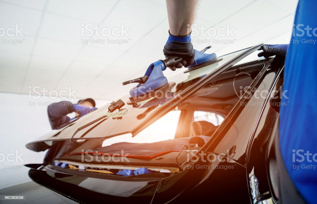 Automobile special workers replacing windscreen or windshield of a car in auto service station garage. stock photo