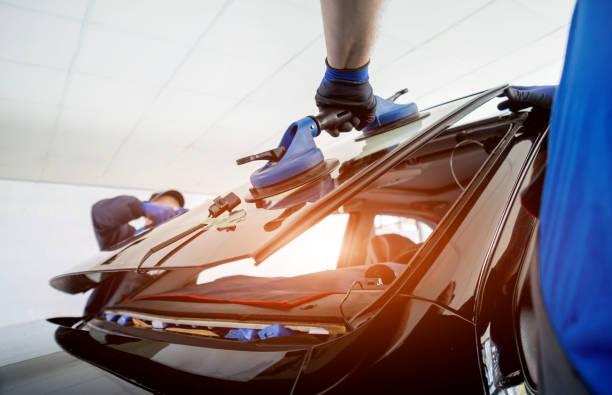 auto speciale werknemers ter vervanging van de voorruit of voorruit van een auto in auto service station garage. - voorruit stockfoto's en -beelden