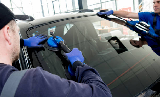 Automobile special workers replacing windscreen or windshield of a car in auto service station garage. Automobile special workers replacing windscreen or windshield of a car in auto service station garage. Background replacement stock pictures, royalty-free photos & images