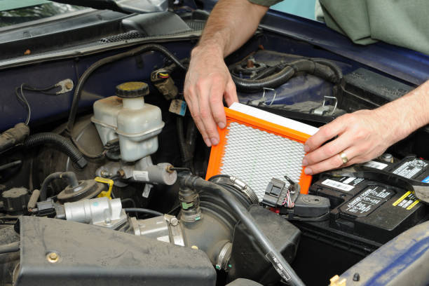 Automotive Air Filter Replacement Man replacing an automotive air filter. air filter stock pictures, royalty-free photos & images