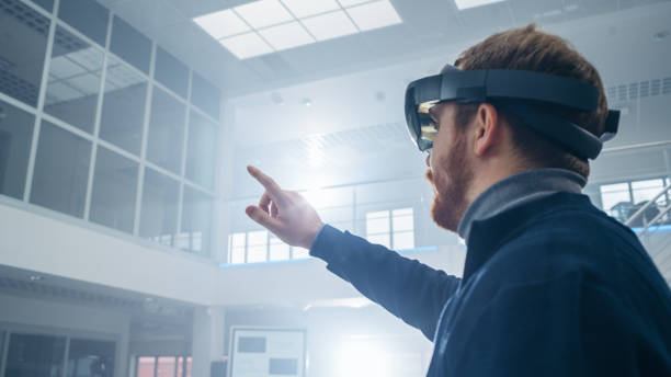 automotive engineer using augmented reality headset and making touching gestures of virtual objects in the air. in innovation high tech laboratory facility with futuristic atmosphere. - realtà aumentata foto e immagini stock