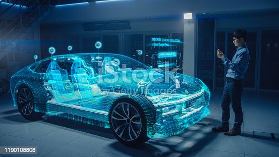 Automotive Engineer Using Digital Tablet Computer with Augmented Reality 3D Software for 3D Car Model Design Analysis and Improvement. Futuristic Facility: Virtual Design with Mixed Technology.