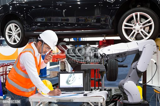 istock Automotive engineer with assistance robotic inspec modern car, Industry 4.0 664692336