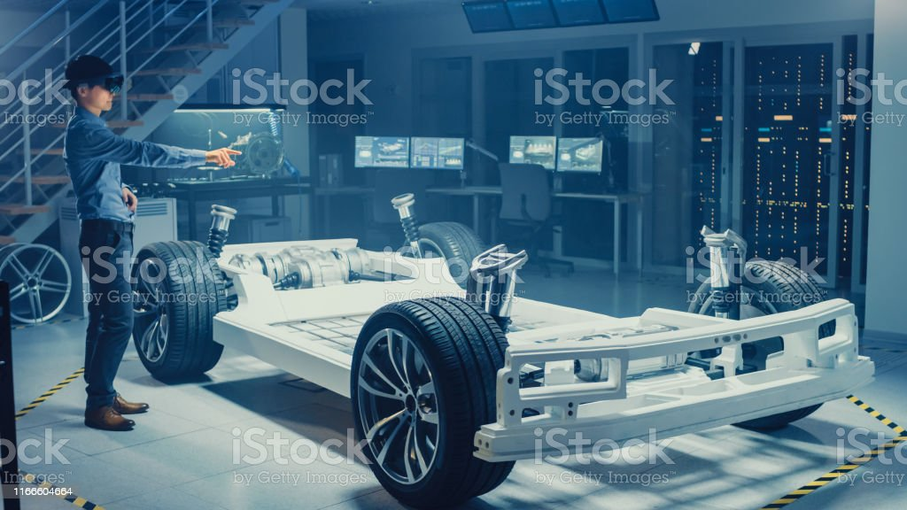 Automotive Engineer Working On Electric Car Chassis Platform Using Augmented Reality Headset And Making Gestures In Innovation Laboratory Facility Concept Vehicle Frame With Wheels Stock Photo Download Image Now Istock