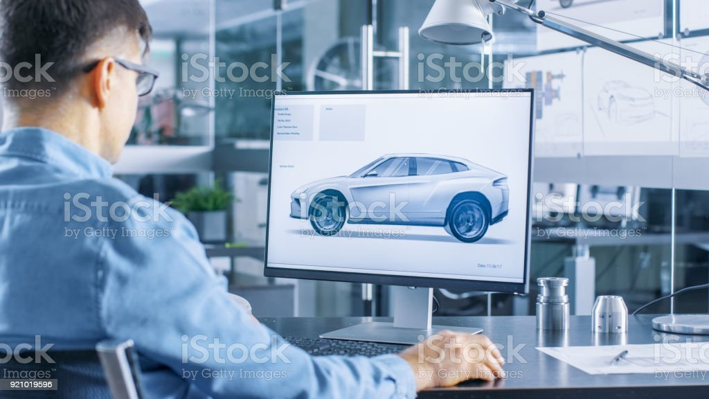 Automotive Engineer Works on the Personal Computer, He Perfects New Car Model Prototype Sketch. He Works in the Bright and Modern Office. stock photo