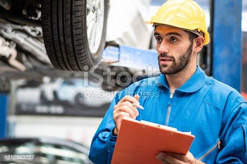 automotive mechanic man checking damage part under car condition, vehicle maintenance technician write on checklist document in garage at auto repair shop on lifter hoist. after service concept