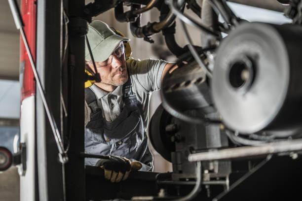 Automotive Mechanic Performing Scheduled Diesel Engine Service stock photo