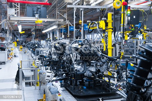 1069360792 istock photo Automotive mechanical assembly, engine, transmission, suspension and breaking system. Automotive engine assembly line is in production. Car Assembly by parts 1072287412