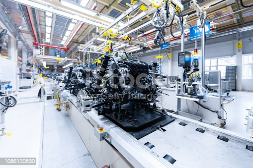 1069360792 istock photo Automotive mechanical assembly, engine, transmission, suspension and breaking system. Automotive engine assembly line is in production. Car Assembly by parts 1086130530