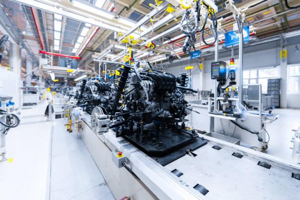 automotive mechanical assembly, engine, transmission, suspension and breaking system. automotive engine assembly line is in production. car assembly by parts - linia produkcyjna zdjęcia i obrazy z banku zdjęć