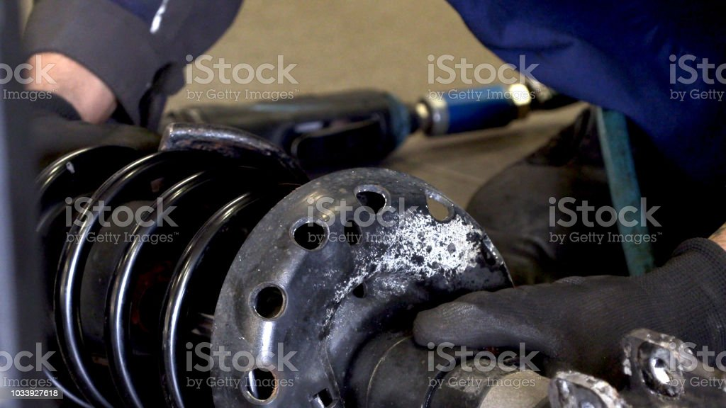 Automotive mechanics repair the shock absorber on the vehicle.