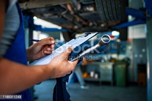 Unrecognizable Male mechanic under car preparing checklist in workshop. Photo of mechanic taking notes under a car.