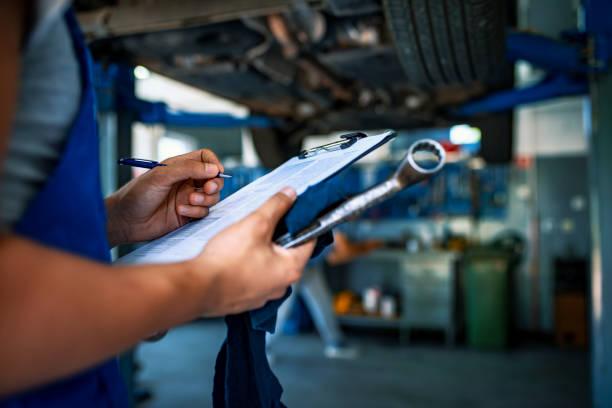 automobilspezialist beim einstellen eines motors - autowerkstatt stock-fotos und bilder