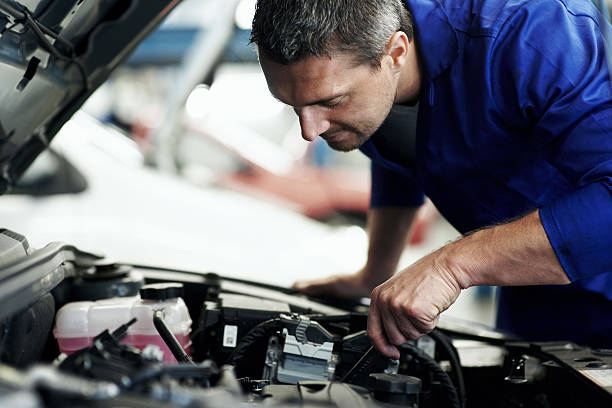 Automotive specialist adjusting an engine stock photo
