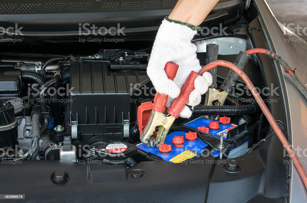 automotive technician charging vehicle battery stock photo