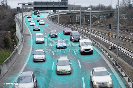 Photo illustration of autonomous self-driving cars using artificial intelligence to drive on a highway. They are connected through a network.
