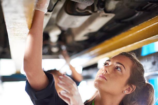 autoshop female mechanic working under a car stock photo