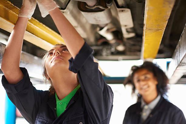 autoshop female tutor assessing a female student. stock photo