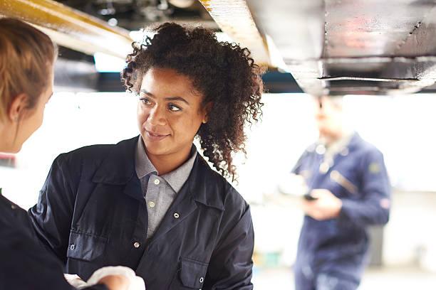 autoshop female tutor talking to a female student. stock photo
