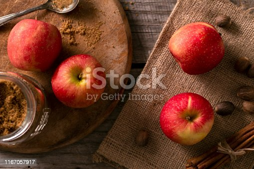 Autumn apples, brown sugar, nutmeg apple pie ingredients on rustic farm house table.