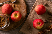 Autumn apples, brown sugar, nutmeg apple pie ingredients on rustic farm house table.