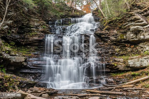 The streaming waters of Kitchen Creek fall like a veil over shale rock and past the autumn colors at Erie Waterfall in Ricketts Glen State Park of Pennsylvania.