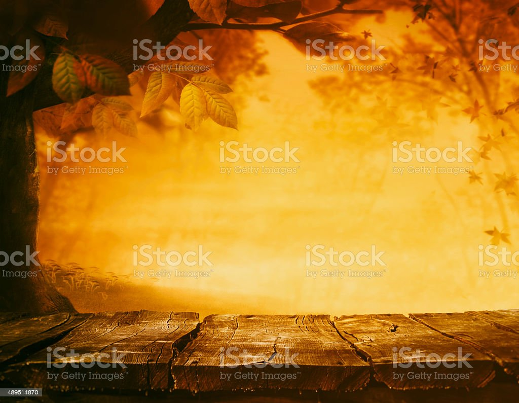 Wooden table. Autumn design with leaves falling in forest and empty...