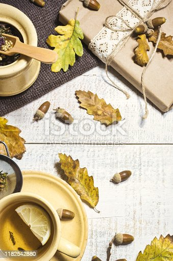 A cup of hot tea with lemon, gift, acorns and autumn leaves on wooden background, top view. Autumn concept background.