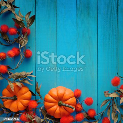 istock Autumn background with pumpkins on blue woods 186668500