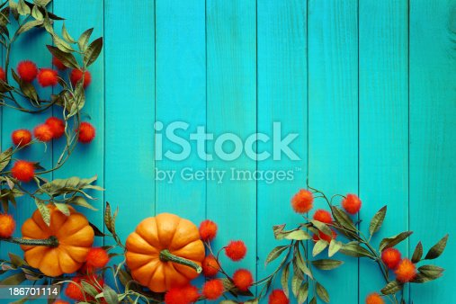 istock Autumn background with pumpkins on turquoise woods 186701114