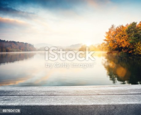 Empty wooden bench by the autumn lake.