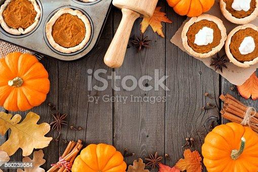istock Autumn baking frame with pumpkin pie tarts over wood 860239584