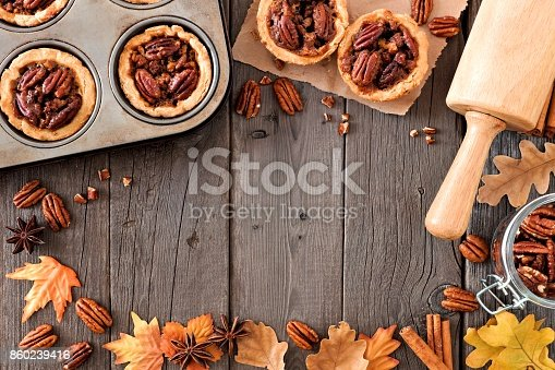 istock Autumn baking scene frame with pecan tarts over wood 860239416