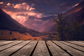 istock Autumn beautiful background with sunset over mountains and empty wooden table in nature outdoor. Natural template landscape 1279157366