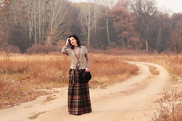 autumn. beautiful young girl on a road of wild field. - damen rock braun stock-fotos und bilder