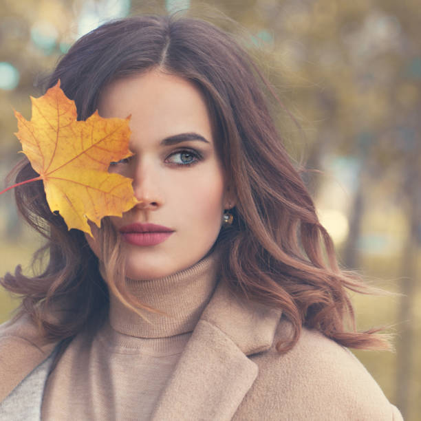Autumn Beauty. Perfect Woman Fashion Model with Fall Mapple Leaf Outdoors stock photo