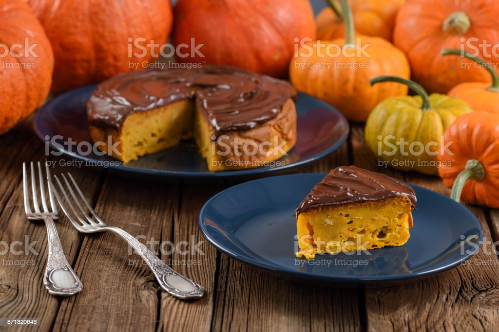 Autumn birthday cake with chocolate icing on navy blue plates decorated with bright orange pumpkins on rustic background stock photo