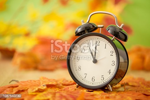 istock Autumn Black vintage clock with dried maple leaves on wooden 1037540230