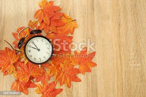 istock Autumn Black vintage clock with dried maple leaves on wooden 1037540432