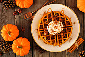 Pumpkin spice waffle with whipped topping, caramel and pecans. Top view table scene on a dark wood background. Autumn breakfast concept.