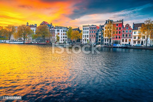 Popular travel and touristic destination. Picturesque autumn cityscape with traditional dutch houses. Water canal with houseboats at sunset, Amsterdam, Netherlands, Europe