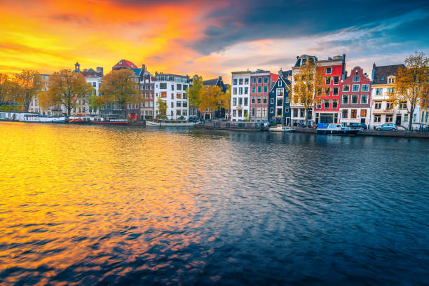 Autumn cityscape and water canal with houseboats in Amsterdam, Netherlands stock photo