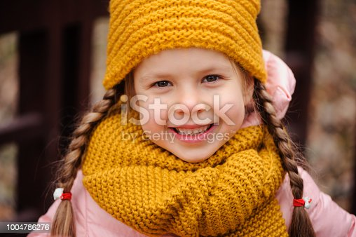 istock autumn close up portrait of happy little child girl enjoying the walk in sunny park in warm knitted hat and scarf 1004786276