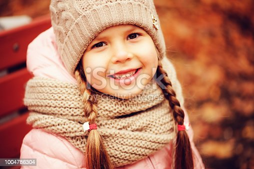 istock autumn close up portrait of happy little child girl enjoying the walk in sunny park in warm knitted hat and scarf 1004786304